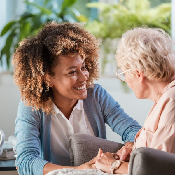 Smiling young female caregiver holding hands and talking with senior woman in living room