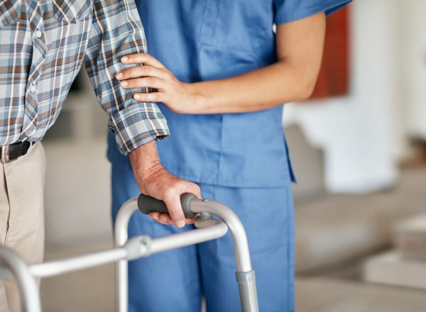 Shot of a woman assisting her elderly patient who's using a walker for support